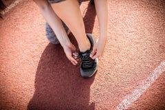 Αθλήτρια που δένει το παπούτσι της μαύρο στενό μαλακό επάνω λευκό μαξιλαριών μικροφώνων ακουστικών απομονωμένο εικόνα Στοκ φωτογραφία με δικαίωμα ελεύθερης χρήσης