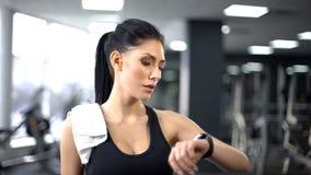 Αθλήτρια που ελέγχει το σφυγμό και τις μμένες θερμίδες στο smartphone, σύγχρονη τεχνολογία στοκ εικόνες