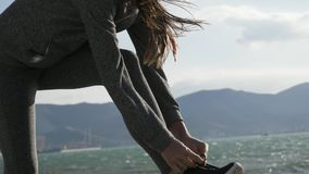 Αθλήτρια που παίρνει έτοιμη για τις δένοντας δαντέλλες τρεξίματος του τρεξίματος των παπουτσιών στην παραλία φιλμ μικρού μήκους