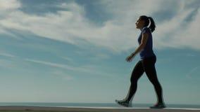 Αθλήτρια που περπατά σε ένα κλίμα ουρανού φιλμ μικρού μήκους