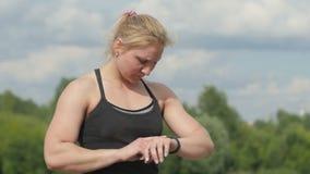 Αθλήτρια υγείας που φορά την έξυπνη συσκευή ρολογιών με την οθόνη αφής που κάνει τις ασκήσεις απόθεμα βίντεο