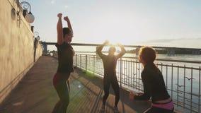 Αθλητές σκιαγραφιών του άλματος ενάντια στον ουρανό με το ηλιοβασίλεμα, σε αργή κίνηση απόθεμα βίντεο