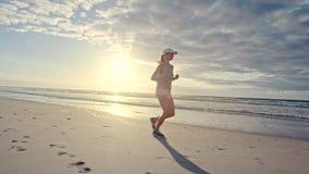 Αθλητής γυναικών που τρέχει κατά μήκος της παραλίας απόθεμα βίντεο