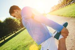 Αθλητής με armband που κάνει τις ασκήσεις θέρμανσης στο πάρκο στο ηλιοβασίλεμα Στοκ Φωτογραφίες