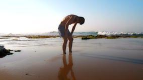 Αθλητής που απεικονίζεται στην υγρή άμμο meditates στην αμμώδη παραλία απόθεμα βίντεο
