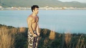 Αθλητής που κάνει τις ασκήσεις με μια λαστιχένια ζώνη ικανότητας σε ένα υπόβαθρο των βουνών και της θάλασσας φιλμ μικρού μήκους