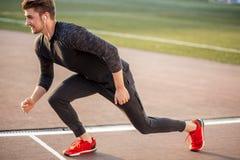 Αθλητής στα μαύρα ενδύματα που αρχίζουν την ορμή στο τρέξιμο της διαδρομής στοκ φωτογραφία με δικαίωμα ελεύθερης χρήσης