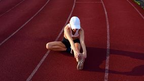 Αθλητικά πόδια τεντώματος γυναικών πριν από το τρέξιμο στο τρέξιμο της διαδρομής φιλμ μικρού μήκους