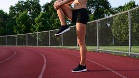 Αθλητικά πόδια τεντώματος γυναικών πριν από το τρέξιμο στο τρέξιμο της διαδρομής απόθεμα βίντεο