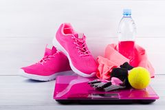 Αθλητικά ρόδινα πάνινα παπούτσια και στοιχεία και ηλεκτρονικές κλίμακες, σε ένα γκρίζο υπόβαθρο στοκ εικόνες