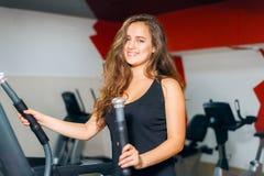 Αθλητικά τραίνα κοριτσιών στο stepper προσομοιωτή Γυναίκα στο χαμόγελο γυμναστικής στοκ εικόνα