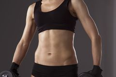Αθλητική γυναίκα που αντλεί επάνω muscules με τους αλτήρες Στοκ φωτογραφία με δικαίωμα ελεύθερης χρήσης