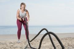 Αθλητική γυναίκα που τραβά τα σχοινιά στην παραλία στοκ φωτογραφίες με δικαίωμα ελεύθερης χρήσης