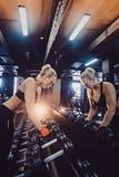 Αθλητική γυναίκα bodybuilder με τους αλτήρες όμορφο ξανθό κορίτσι με τους μυς γυμναστική Στοκ φωτογραφίες με δικαίωμα ελεύθερης χρήσης