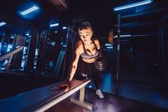 Αθλητική γυναίκα bodybuilder με τους αλτήρες όμορφο ξανθό κορίτσι με τους μυς γυμναστική Στοκ Φωτογραφίες