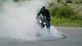 Αθλητική μοτοσικλέτα που αρχίζει να περιστρέφει στην ουδετεροποίηση ασφάλτου και ροδών με τα μέρη του καπνού Σε αργή κίνηση στενό φιλμ μικρού μήκους