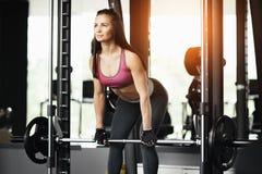 Αθλητική νέα γυναίκα που κάνει deadlift την άσκηση στη μηχανή Smith Στοκ Εικόνες