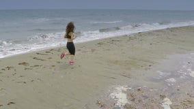 Αθλητική νέα γυναίκα που τρέχει κατά μήκος της κενής παραλίας, ενεργός υγιής τρόπος ζωής, αθλητισμός φιλμ μικρού μήκους