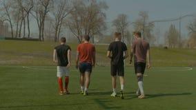 Αθλητική ομάδα που πηγαίνει στην κατάρτιση ποδοσφαίρου στην πίσσα φιλμ μικρού μήκους