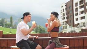 Αθλητική συνεδρίαση ζευγών σε έναν καφέ που απολαμβάνει τους χυμούς μετά από το εντατικό workout φιλμ μικρού μήκους
