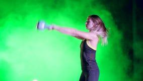 Αθλητική, όμορφη, νέα γυναίκα που κάνει τις διάφορες ασκήσεις δύναμης με τα βάρη Τη νύχτα, λαμβάνοντας υπόψη πολύχρωμο φιλμ μικρού μήκους