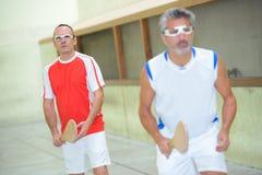Αθλητικοί τύποι που παίζουν το παιχνίδι σφαιρών με τα ξύλινα ρόπαλα Στοκ Φωτογραφίες