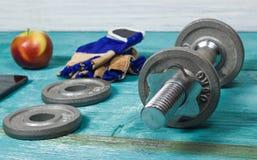 Αθλητικός εξοπλισμός Αλτήρες, ελεύθερα βάρη, αθλητικά γάντια, τηλέφωνο με τα ακουστικά στοκ φωτογραφίες