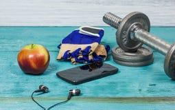 Αθλητικός εξοπλισμός Αλτήρες, ελεύθερα βάρη, αθλητικά γάντια, τηλέφωνο με τα ακουστικά στοκ φωτογραφία