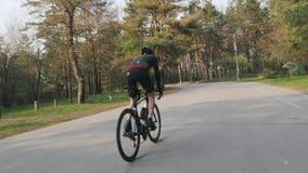 Αθλητικός κατάλληλος ποδηλάτης που τρέχει γρήγορα σκληρά από τη σέλα στο ποδήλατο ανηφορικά Έννοια ανακύκλωσης φιλμ μικρού μήκους