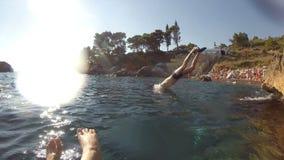 Αθλητικός νεαρός άνδρας που πηδά από τον απότομο βράχο στις ωκεάνιες θαλάσσιου νερού μυϊκές διακοπές χόμπι αθλητικού τρόπου ζωής  φιλμ μικρού μήκους