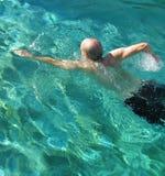 Αθλητικός παλαιότερος ενήλικος αρσενικός κολυμβητής στο ηλιοφώτιστο μπλε νερό Στοκ Εικόνες