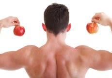 Αθλητικός προκλητικός αρσενικός οικοδόμος σωμάτων που κρατά το κόκκινο μήλο Στοκ εικόνα με δικαίωμα ελεύθερης χρήσης