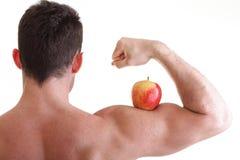 Αθλητικός προκλητικός αρσενικός οικοδόμος σωμάτων που κρατά το κόκκινο μήλο Στοκ Εικόνα
