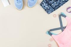 Αθλητικός στηθόδεσμος γυναικών, leggins, πάνινα παπούτσια, ακουστικά και ιχνηλάτης ικανότητας στο ουδέτερο υπόβαθρο Έννοια αθλητι στοκ φωτογραφία
