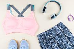 Αθλητικός στηθόδεσμος γυναικών, leggins, πάνινα παπούτσια, ακουστικά και ιχνηλάτης ικανότητας στο ουδέτερο υπόβαθρο Έννοια αθλητι στοκ φωτογραφίες