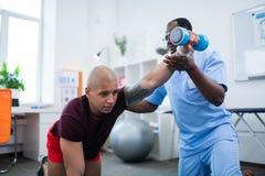 Αθλητικός τύπος που αισθάνεται τον πόνο που ασκεί με τα barbells μετά από τον τραυματισμό στοκ εικόνα