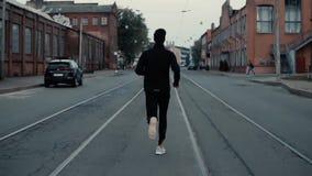 Αθλητικός τύπος που τρέχει μεταξύ των διαδρομών τραμ Πυροβολισμός υποβάθρου κίνηση αργή Έννοια της ισχυρών προσωπικότητας και της απόθεμα βίντεο