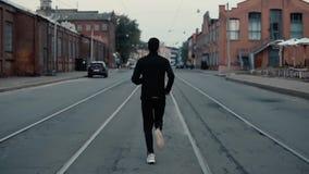 Αθλητικός τύπος που τρέχει στη μέση της οδού Πυροβολισμός υποβάθρου κίνηση αργή Πίσω απόμακρη άποψη μεταξύ των διαδρομών τραμ φιλμ μικρού μήκους