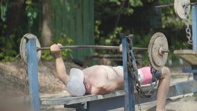Αθλητικό άτομο που αυξάνει το barbell που βρίσκεται στον πάγκο στο πάρκο Άσκηση για τους δικέφαλους μυς Κράτηση του σώματος στη μ απόθεμα βίντεο