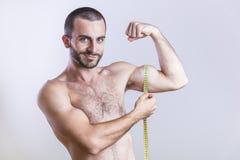 Αθλητικό άτομο που μετρά το μέγεθος δικέφαλων μυών του στοκ φωτογραφία