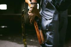 Αθλητικό άτομο στα γκρίζα ενδύματα με ένα πυροβόλο όπλο carbine στο χέρι του στοκ φωτογραφίες με δικαίωμα ελεύθερης χρήσης