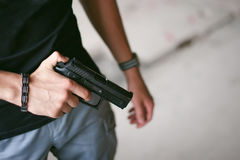 Αθλητικό άτομο στα γκρίζα ενδύματα με ένα πυροβόλο όπλο carbine στο χέρι του στοκ φωτογραφία