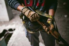 Αθλητικό άτομο στα γκρίζα ενδύματα με ένα πυροβόλο όπλο carbine στο χέρι του στοκ φωτογραφία με δικαίωμα ελεύθερης χρήσης