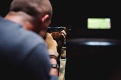 Αθλητικό άτομο στα γκρίζα ενδύματα με ένα πυροβόλο όπλο carbine στο χέρι του στοκ εικόνα