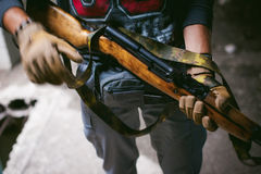 Αθλητικό άτομο στα γκρίζα ενδύματα με ένα πυροβόλο όπλο carbine στο χέρι του στοκ εικόνες