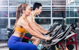 Αθλητικό ασιατικό ζεύγος που κάνει την εσωτερική ανακύκλωση στη γυμναστική στοκ εικόνες με δικαίωμα ελεύθερης χρήσης