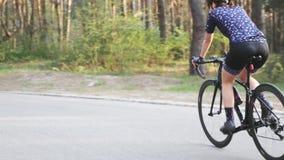 Αθλητικό κατάλληλο θηλυκό ποδηλατών από τη σέλα στο πάρκο Σκληρά εκπαιδευτικός στο ποδήλατο Έννοια οδικής ανακύκλωσης απόθεμα βίντεο