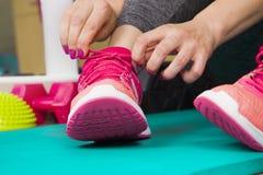 Αθλητικό κορίτσι που δένει τα παπούτσια της, θηλυκός δρομέας που δένουν το prepari παπουτσιών της Στοκ Εικόνες
