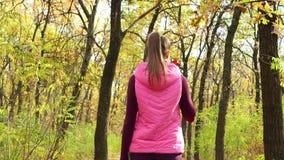 Αθλητικό κορίτσι που περπατά κατά μήκος του πάρκου φθινοπώρου sportswear με το αθλητικό μπουκάλι νερό ή το isotonic ποτό υπό εξέτ φιλμ μικρού μήκους