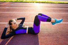 Αθλητικό κορίτσι που συμμετέχεται σε μια προθέρμανση στο στάδιο στο ηλιοβασίλεμα στοκ εικόνα με δικαίωμα ελεύθερης χρήσης